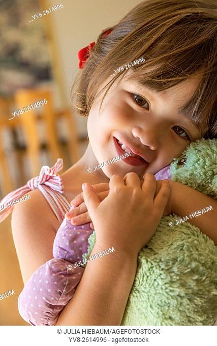 Sweet toddler girl holding her favorite toy