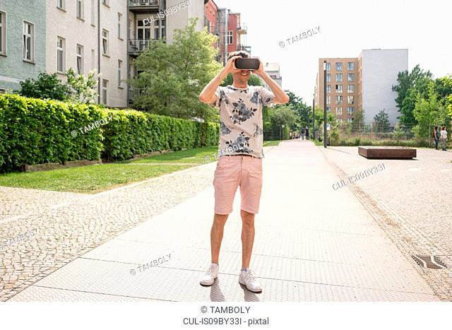 Man using virtual reality goggles in urban Berlin, Germany