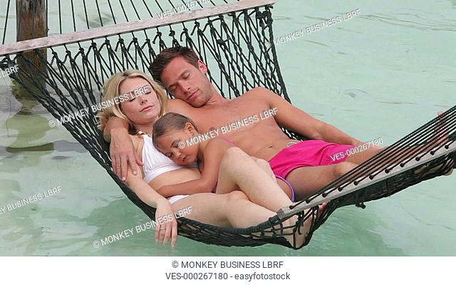 Family lying in hammock with eyes closed.Shot on Canon 5d Mk2 with a frame rate of 30fps