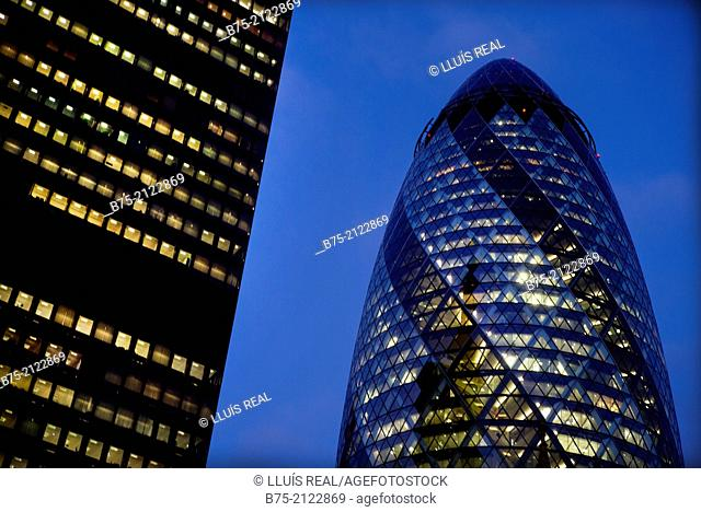 The Gherkin building and an office building of modern architecture with lighted windows at dusk in the city of London, England, UK, Europe
