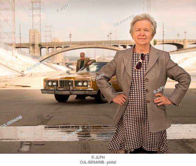 Portrait of cool senior woman and husband with classic car, Los Angeles, California, USA