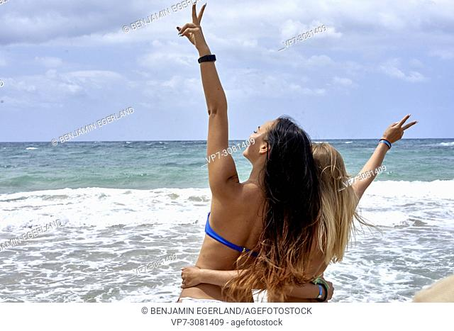 Rear view of two young women at beach in bikini. Malia, Crete, Greece