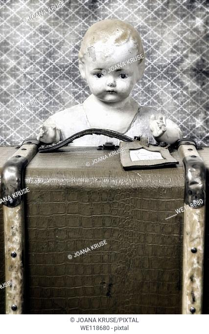 an old doll is looking out of a vintage suitcase