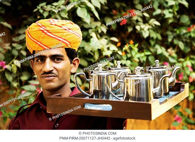 Portrait of a waiter holding the tray of tea kettles, Jodhpur, Rajasthan, India