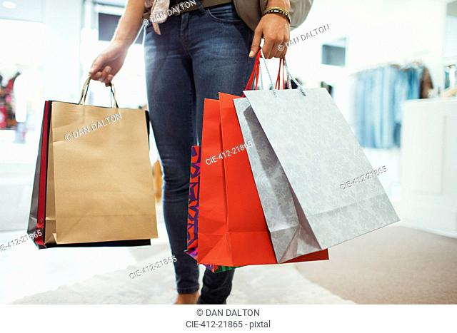 Woman carrying shopping bags in clothing store