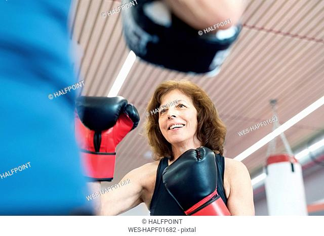 Fit senior woman boxing with her coach