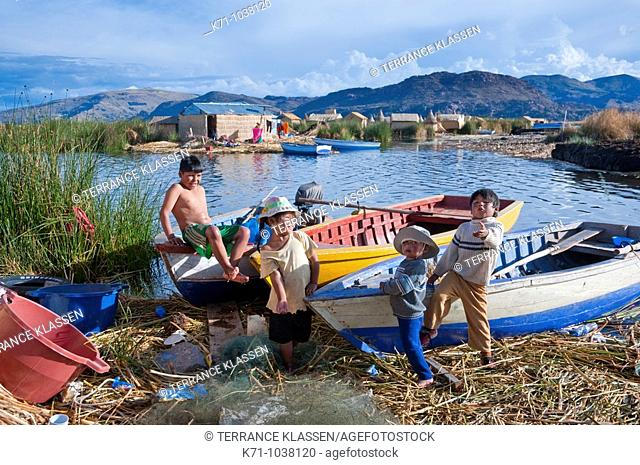 Children playing on the boats at the floating Islands in Lake Titicaca, Peru, South America