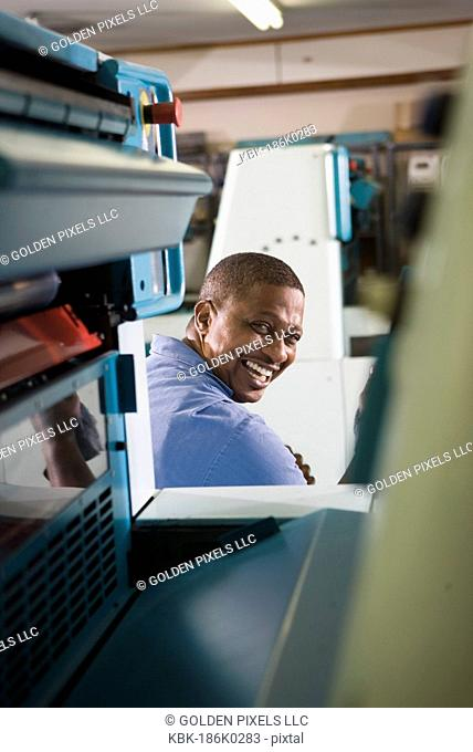 Portrait of a man in coveralls sitting behind a printing machine