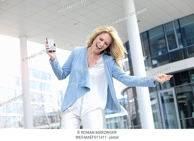 Happy woman listening to music from smartphone