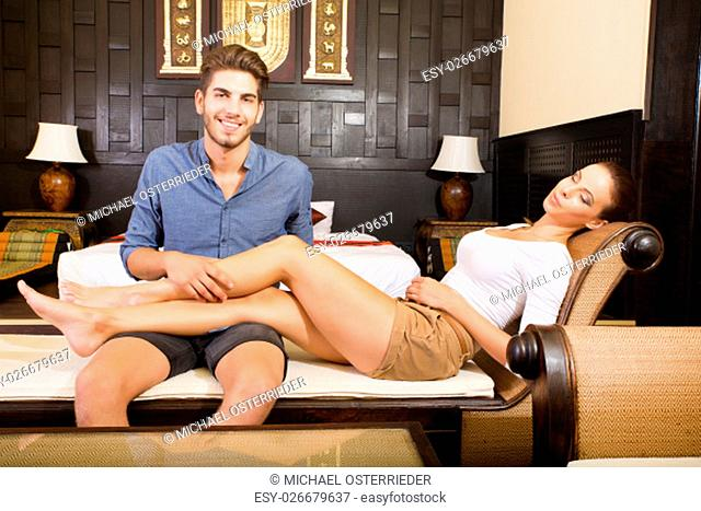 A young and happy couple on holidays enjoying their hotel room.