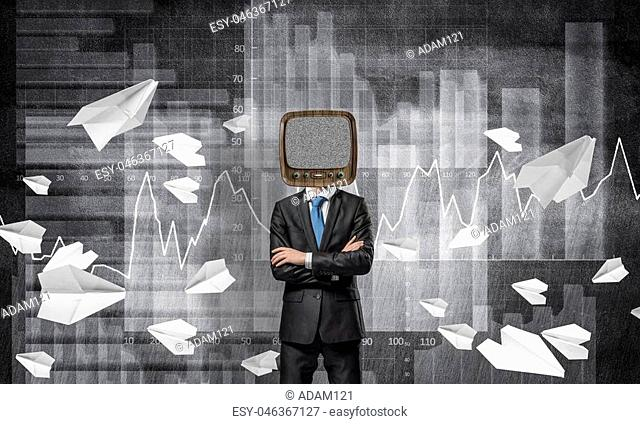 Businessman in suit with old TV instead of head keeping arms crossed while standing against flying paper planes and analytical charts drawn on wall on...