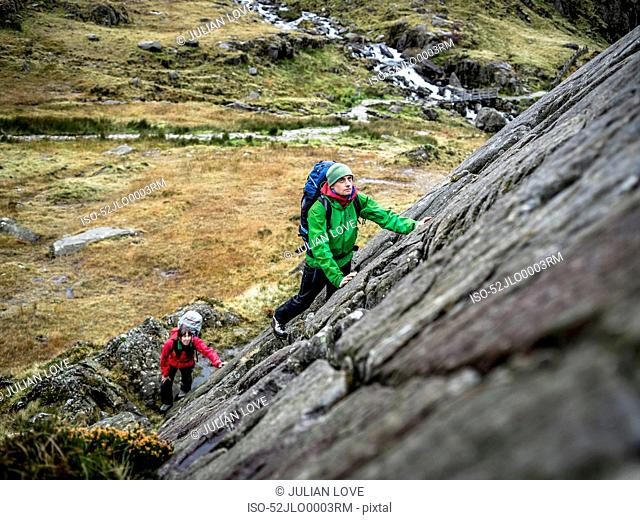 Hikers scaling steep rock face
