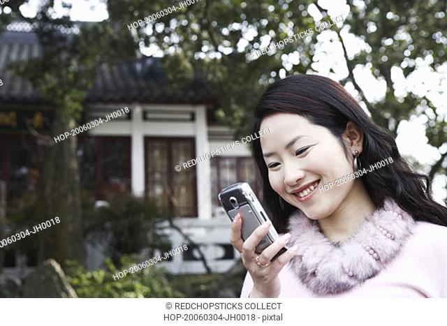 Close-up of a young woman looking at a mobile phone smiling