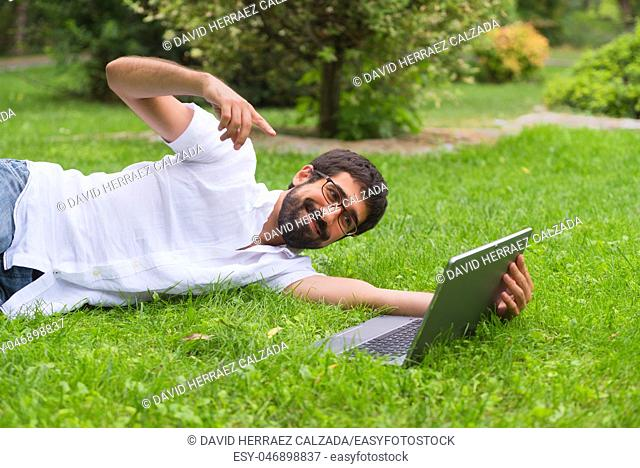 Young man working on his laptop while lying on the grass of the park. Happy expression, concept of freedom