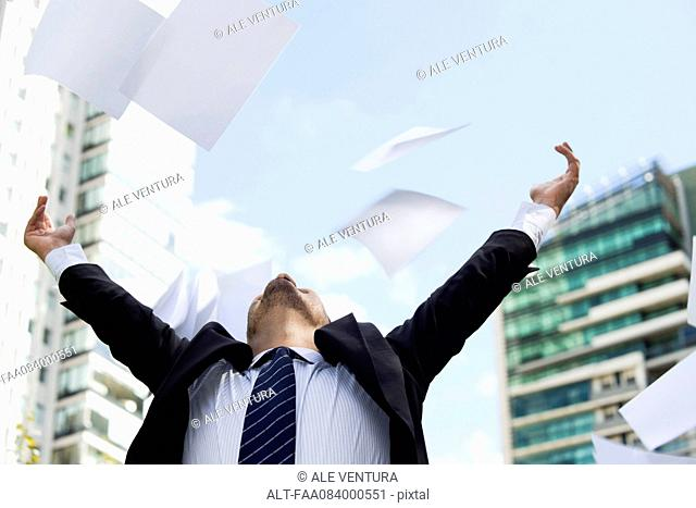 Businessman thrwoing paper in air