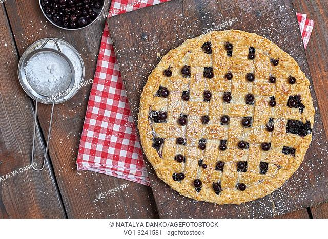 baked round black currant cake on wooden background, top view