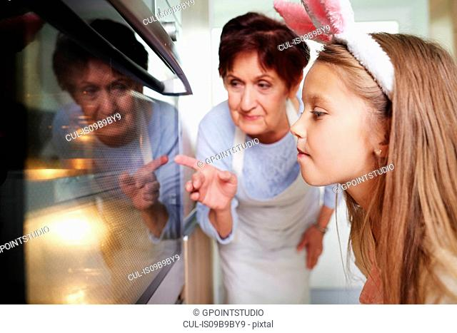 Girl and grandmother watching easter biscuits in kitchen oven