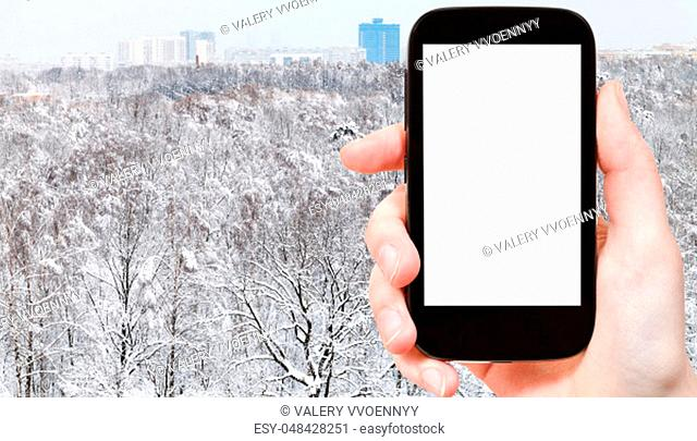travel concept - tourist photographs of snowy city park and residential district in winter in Moscow city on smartphone with empty cutout screen with blank...