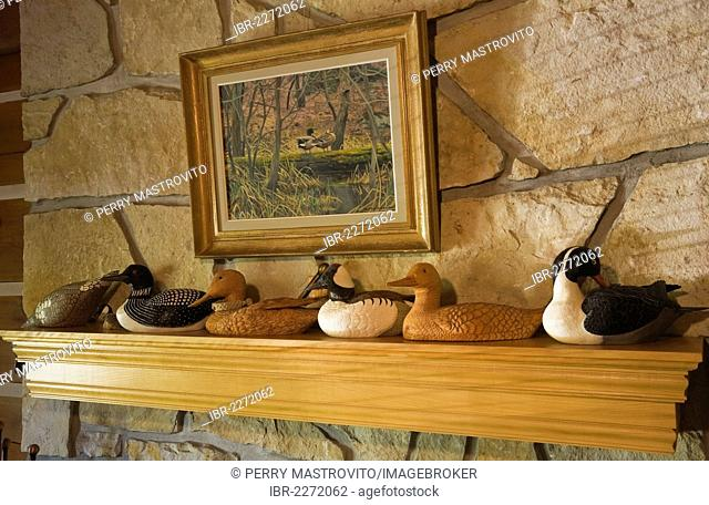 Wooden duck and loon carvings on a fireplace mantle in the living room of a 1977 reproduction of an old Canadiana cottage-style residential log home, Quebec