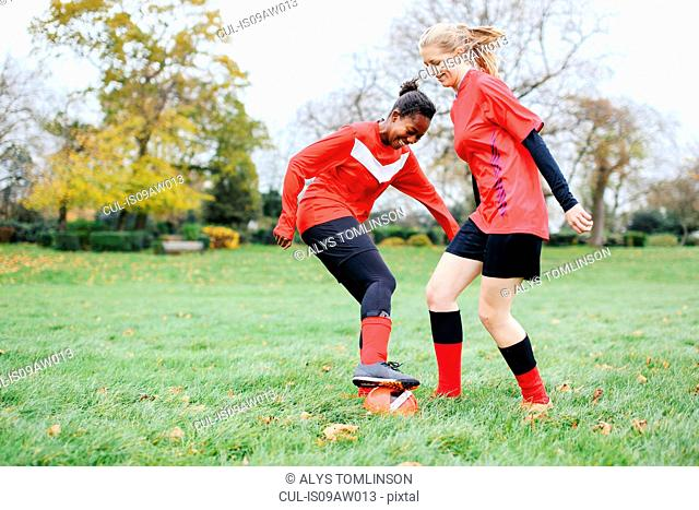 Two female soccer players practicing in park