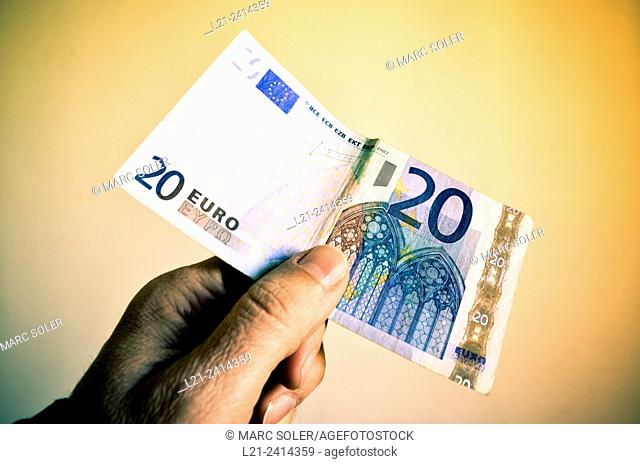 A hand holding 20 euros bank note