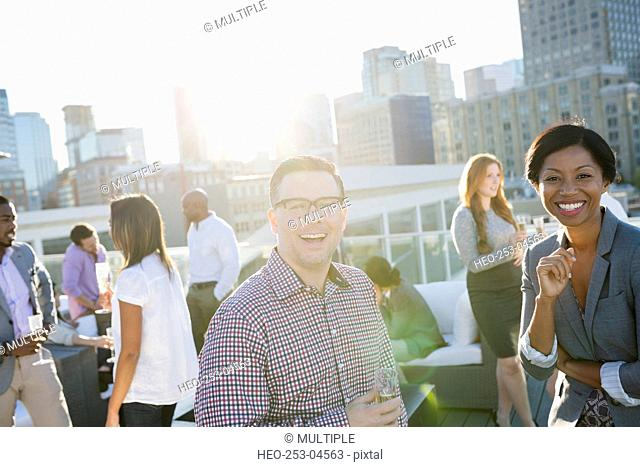 Portrait smiling business people on sunny urban rooftop