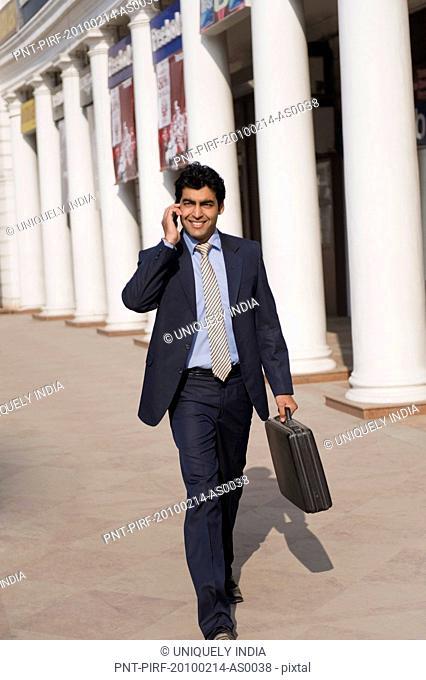 Businessman talking on a mobile phone while walking, Gurgaon, Haryana, India