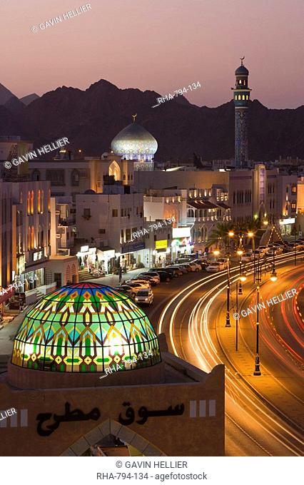 Elevated dusk view along the Corniche, stained glass dome of Mutrah Souq, colourful latticed buildings and Mutrah Mosque, Muscat, Oman, Middle East