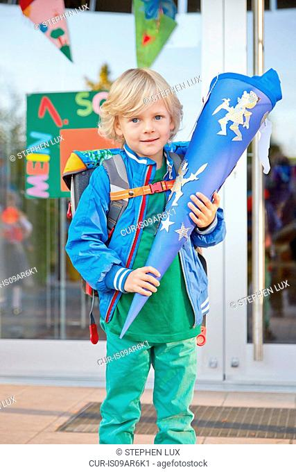 Portrait of young boy on first day of school, holding school cone, Bavaria, Germany