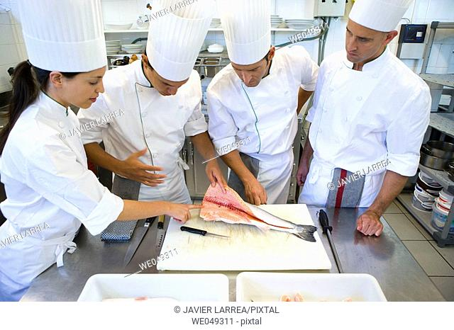 Chefs cutting salmon. Luis Irizar cooking school. Donostia, Gipuzkoa, Basque Country, Spain