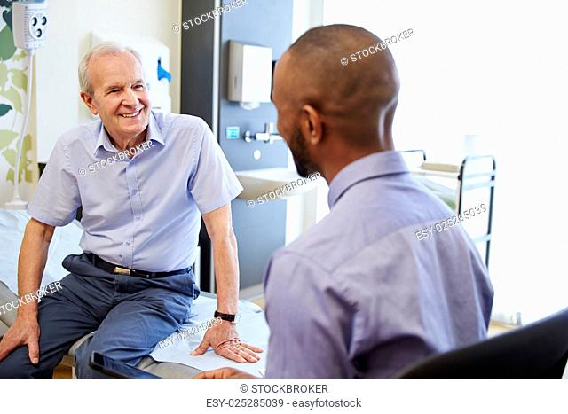 Senior Patient And Doctor Have Consultation In Hospital Room