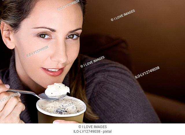 A mid adult woman eating ice cream