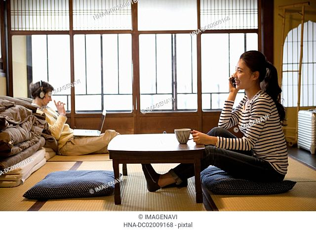 Young Japanese woman talking with smartphone and Caucasian man using laptop