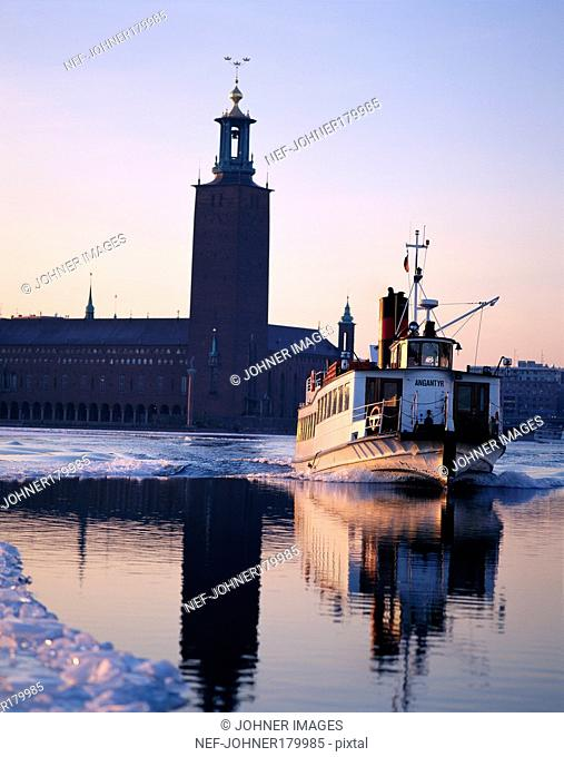 Ship sailing on water against building