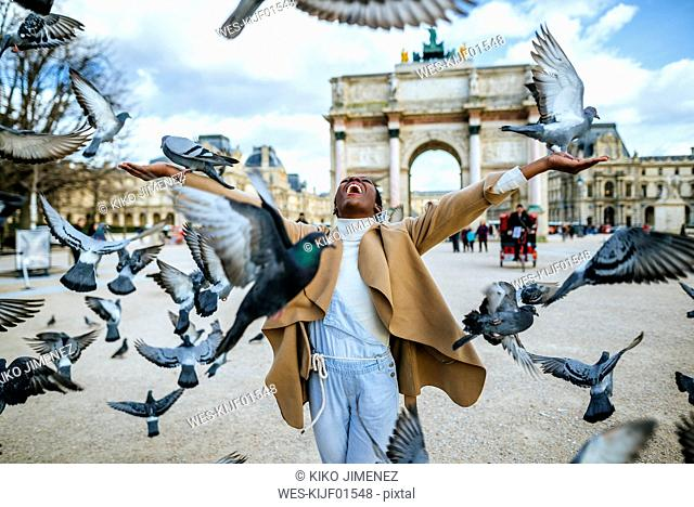 France, Paris, Happy young woman with flying pidgeons at Arc de Triomphe