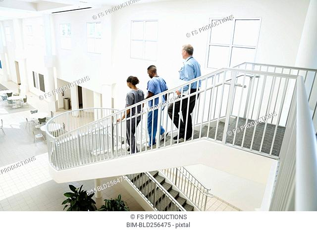 Doctor and nurses descending staircase