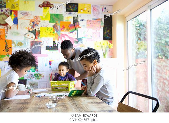 Father and children coloring at dining table