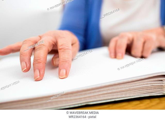 Blind senior woman using braille to read