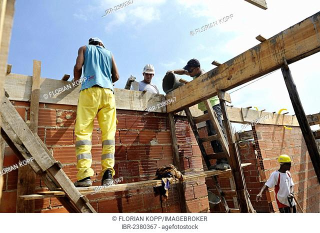 People from the slums, favelas, working together on a construction site of the Esperanca housing co-operative, each family helping out on the project and...