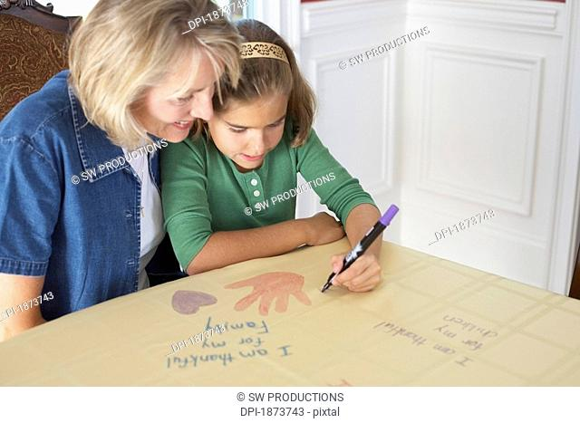 a girl with her mother drawing a picture saying 'i am thankful for my family'