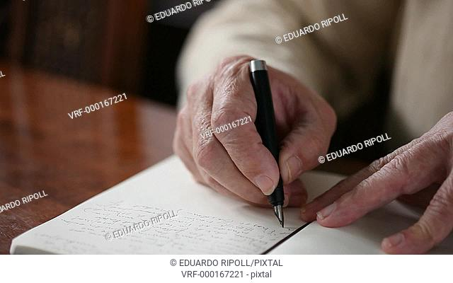 Closeup of a hand writing with a pen on a notebook