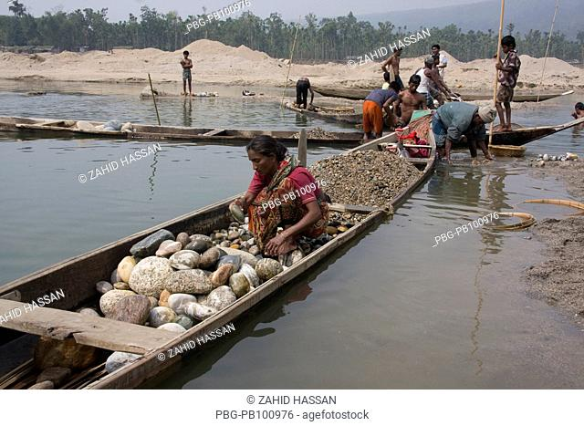 Stone collectors at work on the bank of Mari River in Jaflong, Bangladesh The river coming from the Himalayas of India brings millions of tons of stone boulders...