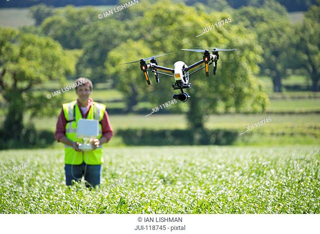 Farmer flying drone to survey crop in field