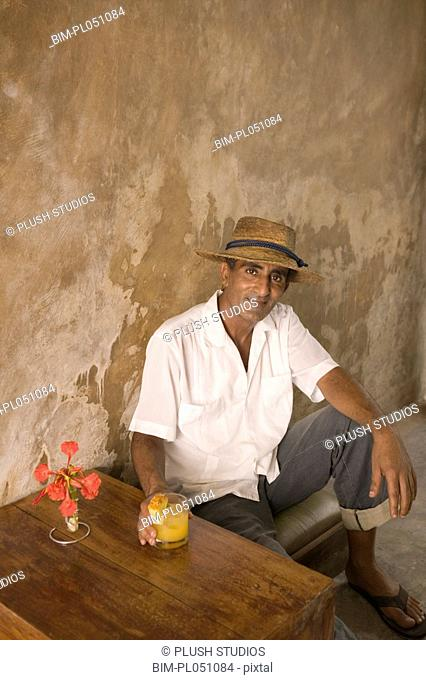 Portrait of man sitting at table with drink