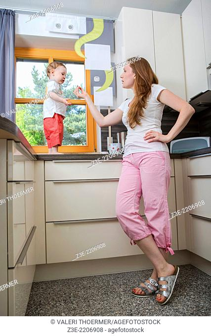 woman with a 1,5 years old boy in the kitchen