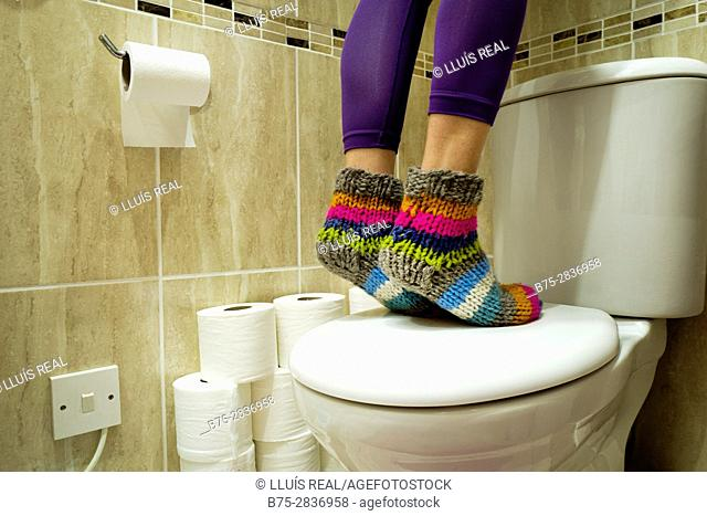Feet of a woman with brightly colored socks standing on a toilet in a bathroom. Buckden, Skipton, North Yorkshire, Yorkshire Dales, England, UK