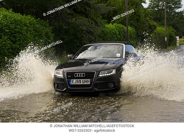 UK Girton -- 14 Jul 2011 -- A car drives through a localised flood in Girton, Cambridgeshire, England. Eastern England suffered widespread flooding problems...