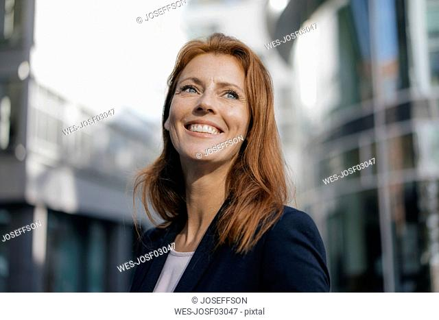 Portrait of smiling businesswoman outdoors in the city