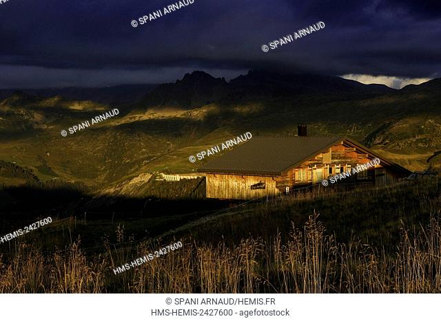 France, Savoie, Beaufortain, Hauteluce, view of a mountain chalet in the pastures under a stormy sky at sunset