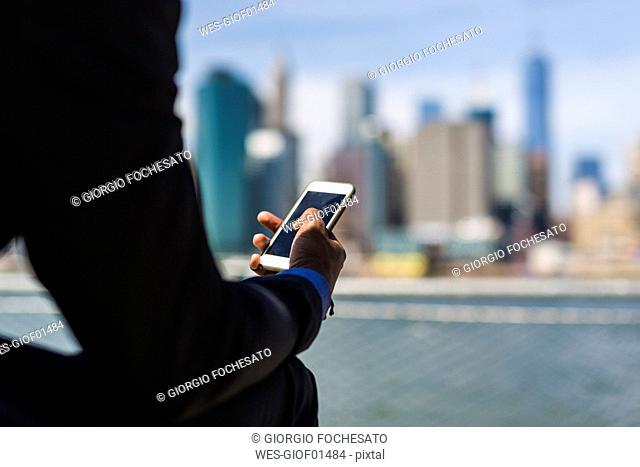 USA, Brooklyn, hand of businessman holding cell phone